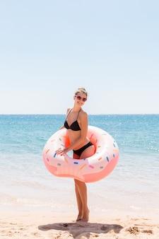 La bella giovane donna in piscina nuota sulla ciambella gonfiabile dell'anello e si diverte con un bicchiere di cocktail in vacanza.