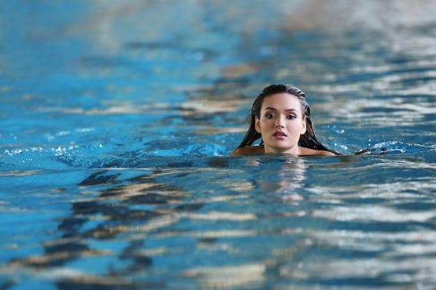 Bella giovane donna che nuota in piscina