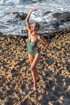 Bella giovane donna in costume da bagno sulla spiaggia.