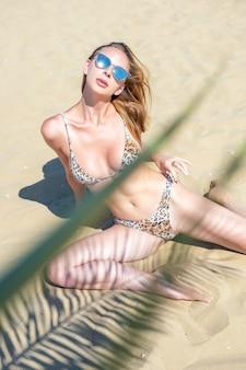Bella giovane donna in costume da bagno in posa su una spiaggia di sabbia.