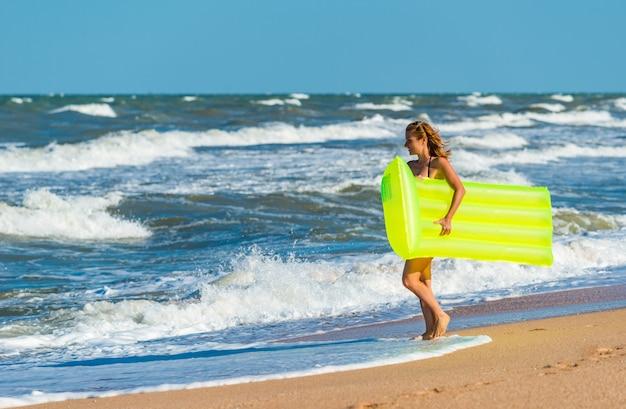 Bella giovane donna in costume da bagno corre lungo la spiaggia con un materasso ad aria tra le mani