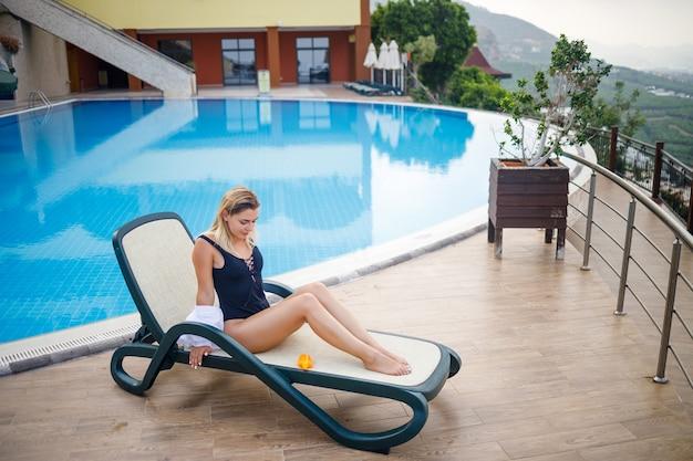 Una bellissima giovane donna in costume da bagno e camicia bianca si siede su un lettino a bordo piscina e si strofina il corpo con la crema solare. cura della pelle estiva, protezione contro le scottature della pelle