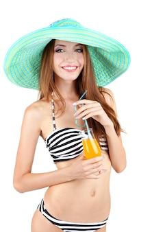 Bella giovane donna in costume da bagno con cocktail su bianco