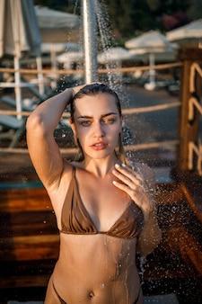 Bella giovane donna in costume da bagno con una figura perfetta sotto la doccia alla luce del tramonto in riva al mare. ragazza dall'abbronzatura dorata in vacanza