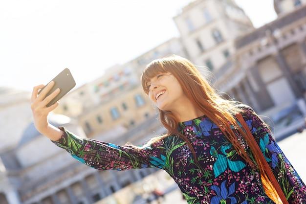 La bella giovane donna prende un selfie a napoli.