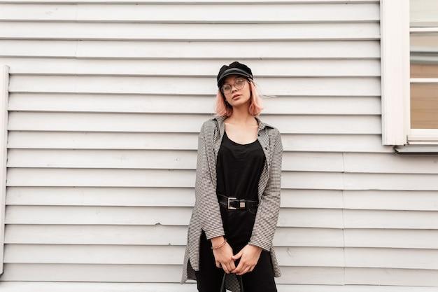 Bella giovane donna adolescente in abiti casual alla moda con occhiali vintage e un cappello si trova vicino a un muro di casa in legno