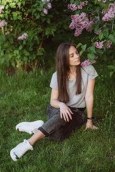 Bella giovane donna, ragazza adolescente, vicino a un cespuglio di lillà in un soleggiato parco primaverile. messa a fuoco selettiva morbida.