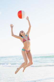 Bella giovane donna che getta un pallone da spiaggia