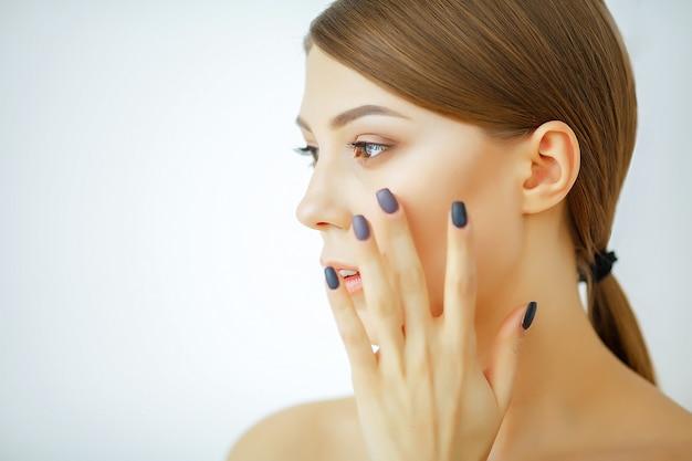Bella giovane donna che tocca il suo viso pulito con una pelle fresca e sana