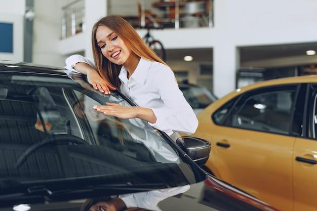 Bella giovane donna che tocca la sua nuova automobile con piacere