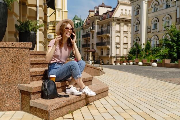 Turista della bella giovane donna con caffè da portar via che si siede sulle scale facendo uso dello smartphone