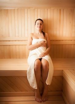 Bella giovane donna in asciugamano che si rilassa alla sauna