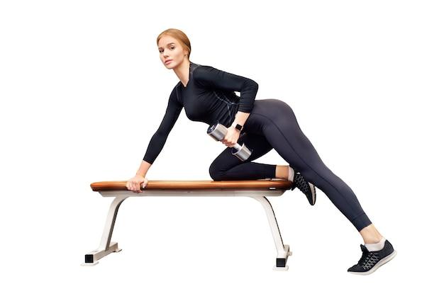 La bella giovane donna allena il deltoide sul banco in palestra isolata su bianco