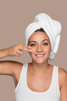 Bella giovane donna che prova i prodotti cosmetici