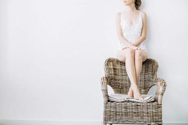 Bella giovane donna in biancheria intima sulla sedia di paglia vicino al muro bianco.
