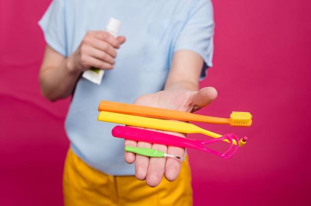 La bella giovane donna utilizza un kit per l'igiene orale composto da un raschietto per lingua singolo trapuntato e uno spazzolino interdentale