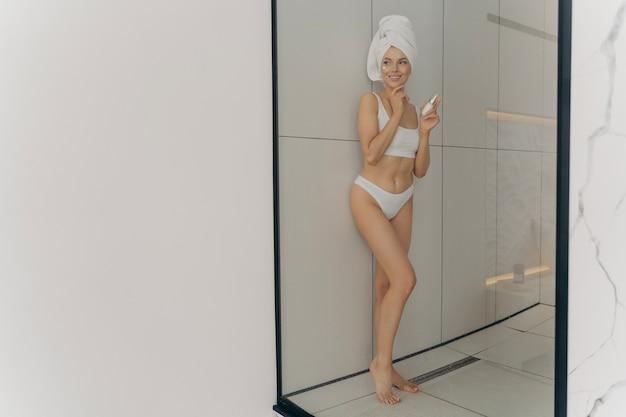 Bella giovane donna che usa un prodotto cosmetico per una pelle sana e sorride mentre posa nel bagno di casa, fa la routine di bellezza dopo la doccia mattutina, indossa un asciugamano avvolto sulla testa e lingerie bianca