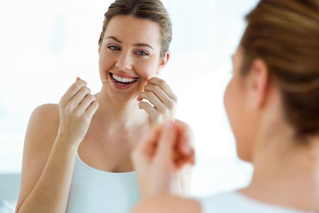 Bella giovane donna che utilizza il filo per i denti in un bagno domestico.