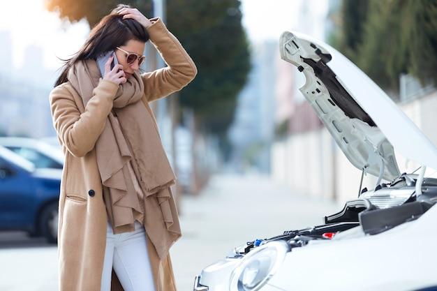 La bella giovane donna che usando il suo telefono cellulare richiede assistenza per l'automobile