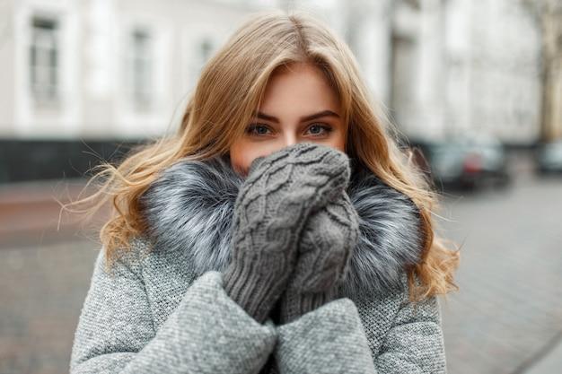 Bella giovane donna in guanti a maglia vintage nasconde il viso dal freddo