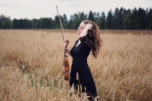 Una violinista bella giovane donna in piedi in un campo di grano raddrizza i suoi magnifici capelli che sono stati portati via dal vento