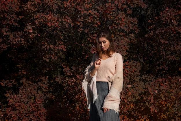 Bella giovane donna che cammina nella foresta di autunno. tempo caldo e soleggiato