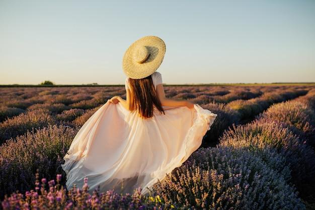 Bella giovane donna che cammina il campo di lavanda in provenza, francia.
