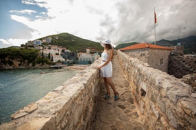 Bella giovane donna che cammina sopra il muro di pietra al vecchio castello