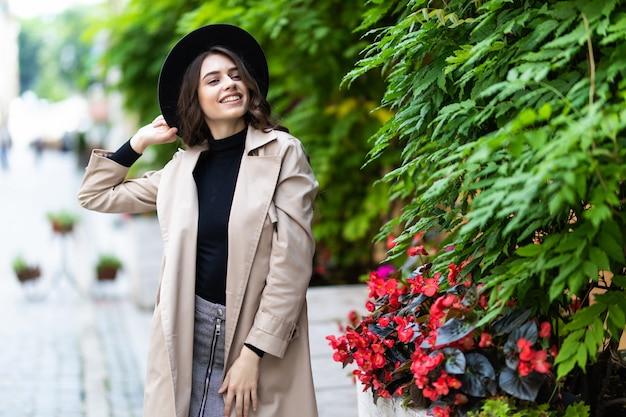 Bella giovane donna indossa cappello e cappotto a piedi in città.