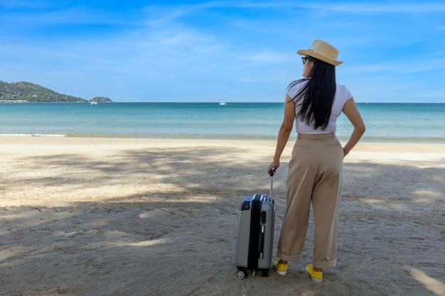 Bella giovane donna indossa t-shirt, pantaloni lunghi e cappello di paglia con una valigia su una spiaggia tropicale.