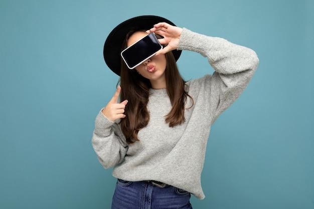 Bella giovane donna che indossa cappello nero e maglione grigio che tiene il telefono che mostra smartphone