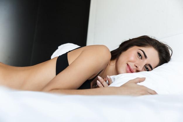 Bella giovane donna che indossa lingerie nera posa sul letto