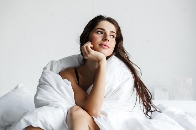 Bella giovane donna che indossa lingerie nera seduta sul letto coperto di coperta