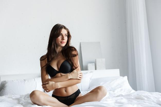 Bella giovane donna che indossa lingerie nera seduta sul letto