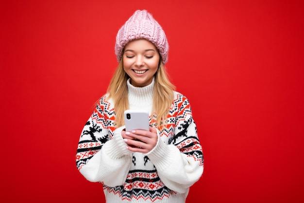 Bella giovane donna che indossa abiti casual in piedi isolato su sfondo navigazione su internet tramite telefono guardando lo schermo del cellulare.