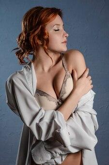 Bella giovane donna che indossa lingerie casual e camicia bianca sulla parete blu