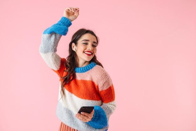 Bella giovane donna che indossa abiti colorati in piedi isolato su rosa, ascoltando musica con gli auricolari, tenendo il telefono cellulare