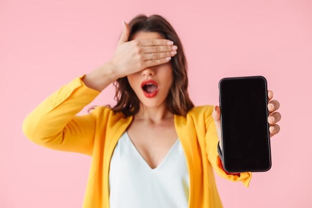 Bella giovane donna che indossa abiti colorati in piedi isolato su rosa, mostrando il telefono cellulare con schermo vuoto