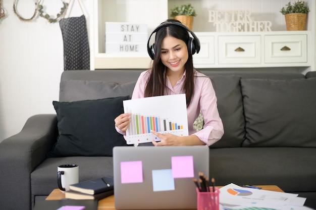 Una bella giovane donna che indossa l'auricolare sta effettuando una videoconferenza tramite computer a casa, concetto di tecnologia aziendale.