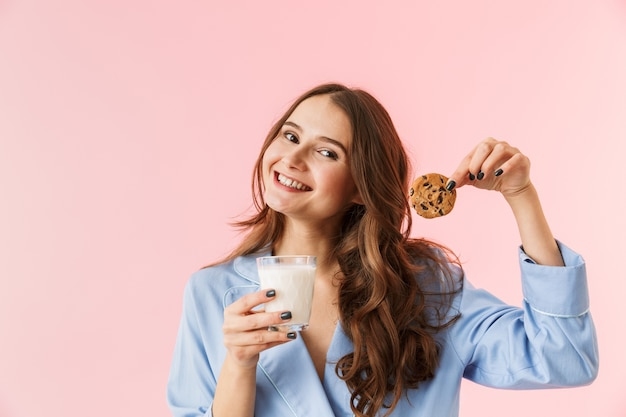 Bella giovane donna che indossa un pigiama in piedi isolato su sfondo rosa, mangiare biscotti al cioccolato, bere latte