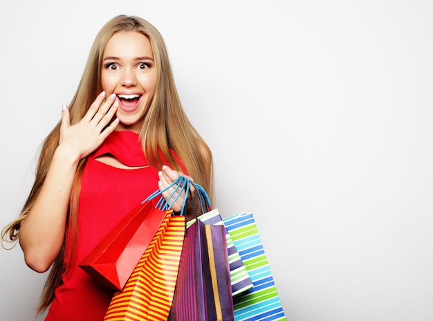 Bella giovane donna che indossa un abito rosso con borse della spesa. grande vendita.