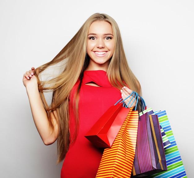 Bella giovane donna che indossa un abito rosso con borse della spesa.