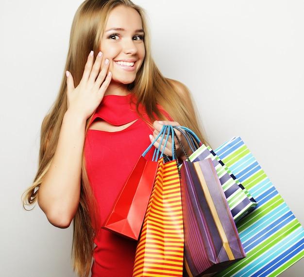 Bella giovane donna che indossa un abito rosso con borse della spesa