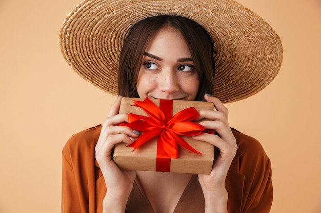 Bella giovane donna che indossa un cappello di paglia e un vestito estivo in piedi isolato su un muro beige, mostrando una confezione regalo