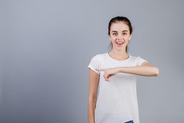 Camicia bianca da portare della bella giovane donna con la coda di cavallo che indica al copyspace con le dita isolate sopra grey