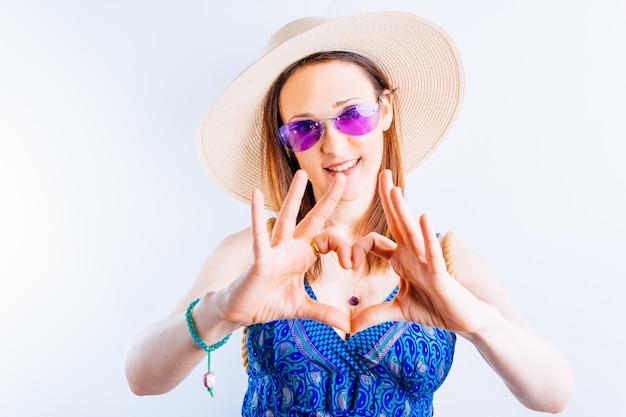 Bella giovane donna su sfondo bianco che fa un cuore con le mani vestite con cappello di paglia, vestito e occhiali estivi viola. concetto di arrivo dell'estate amore per l'estate