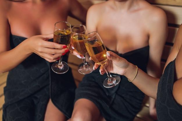 Bella giovane donna in accappatoio bianco bevendo champagne in sauna.