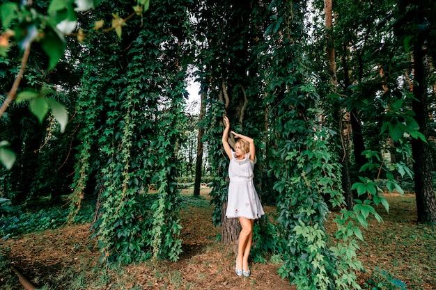 Bella giovane donna in vestito bianco che posa nel parco con le liane