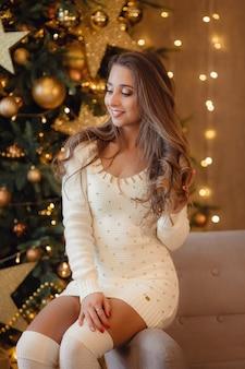 Bella giovane donna in un abito bianco lavorato a maglia e calze vicino a un bellissimo albero di natale in gioielli d'oro. l'idea e il concetto di felice natale e capodanno