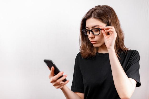 La bella giovane donna su bianco esamina il telefono con gli occhiali e una camicia nera. copyspace.